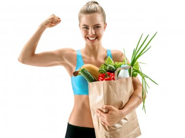 Happy cute athletic woman showing biceps with grocery bag full of healthy fruits and vegetables