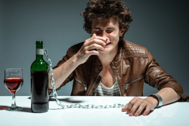 Alcoholic drunk man drinking wine, feeling depressed, falling into addiction problem