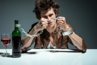 Portrait of a lonely and desperate drunk man trying to break the chains