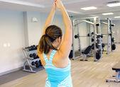 Sportovní žena natahovat ruku, v tělocvičně