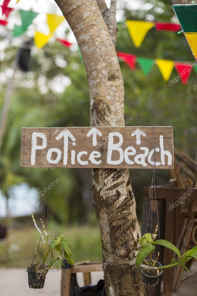 Police beach wooden sign hanging on a tree on Koh Rong Island