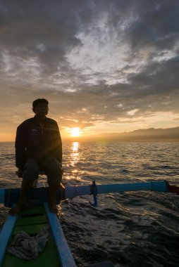 Fisher man, traditional wooden boat and ocean view during sunris