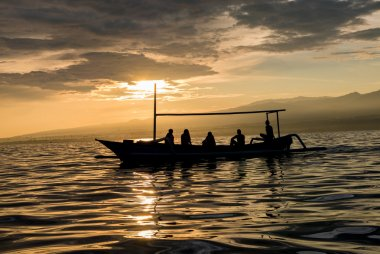 Amazing sunrise with silhouette of people in small boat in Lovin