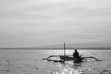 Fisher man, traditional wooden boat and ocean view, Bali. black
