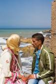 Young Moroccan  couple sitting at the old fort of Essaouira