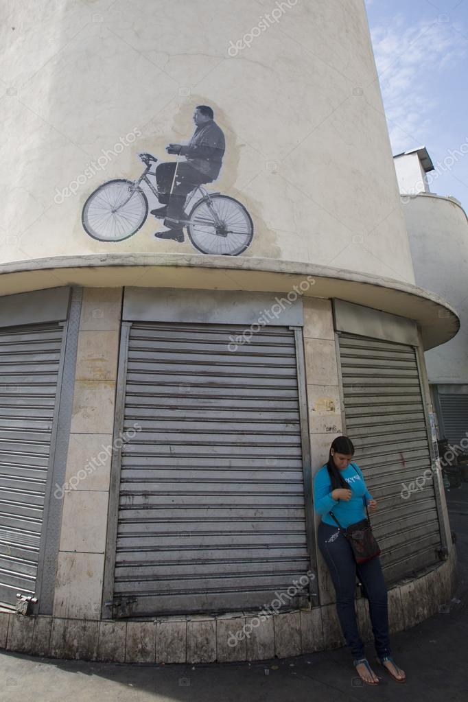 Woman waiting with a drawing of Hugo Chavez on a bike on top. Ca