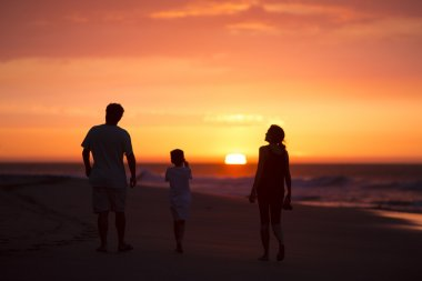 silhouette of family on the beach at dusk in Peru