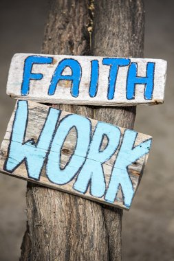 Faith and work wooden signs on tree trunk in Mancora, Peru