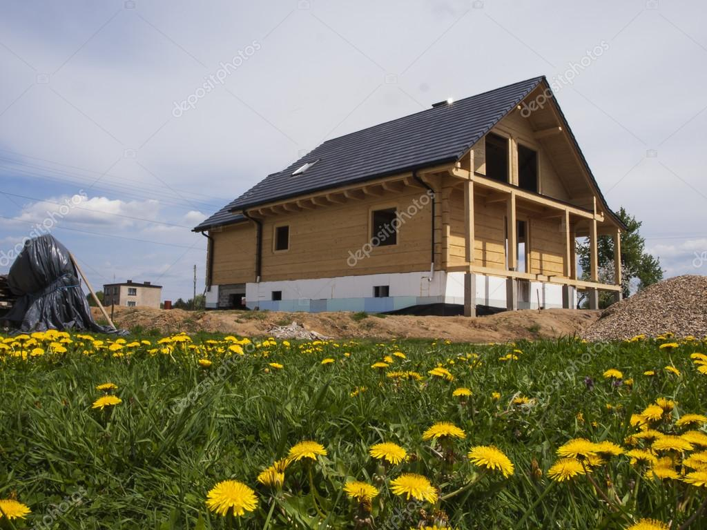 Construction Of A Wooden House And Yellow Dandelions In The Meadow