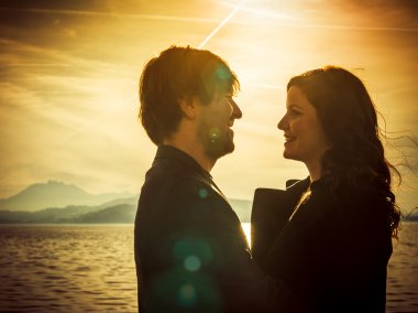 Couple standing by the lake in the sunlight