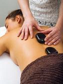 Masážní terapeut uvádění horké kameny