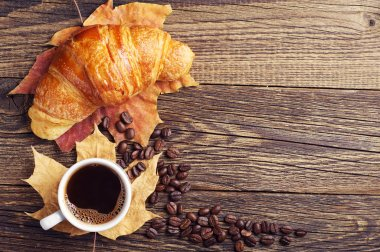 Coffee, croissant and autumn leaves