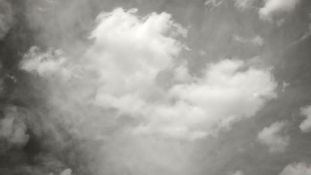 Timelapse pěkné bílé mraky ve slunečný den běží ve dvou různých směrech - cumulus a stratus v černé a bílé - full hd