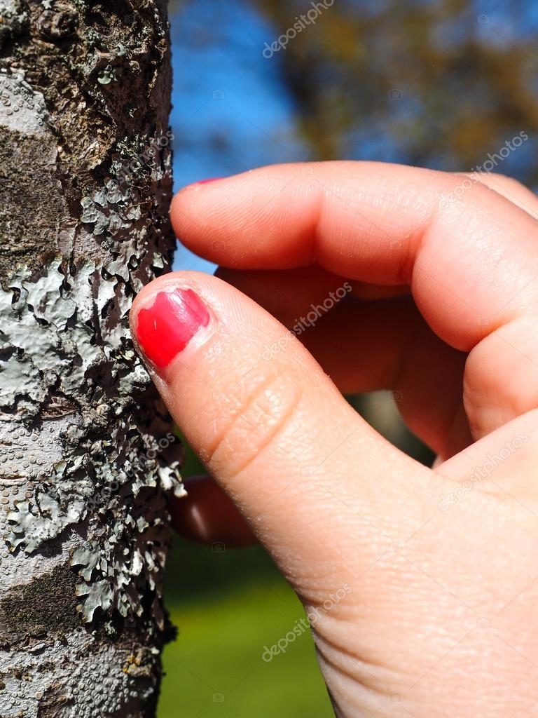 Kleines Mädchen mit gebrochenen Rosa Nagel Farbe berühren Flechte ...