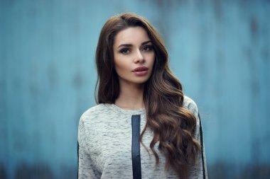 Pretty girl in hoodie against blue wall