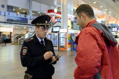 A police officer checks the citizen's information database at the entrance to the Moscow airport.