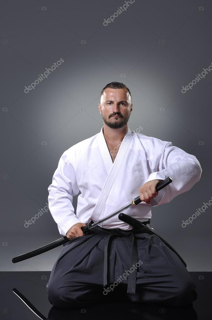Handsome young black belt male karate posing with sword on the gray