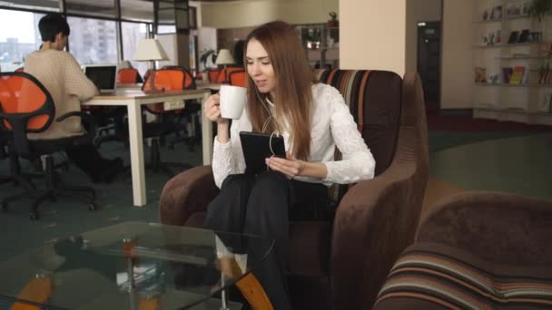 Young Woman  Speaking On The Touch Screen Tablet And Drinking Coffee