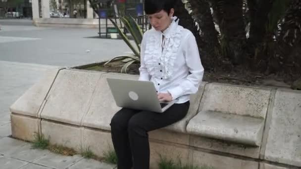 Gépelés-on számítógép kültéri álló üzletasszony.