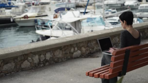 Woman with short black hair working on the laptop outdoor near the harbour.