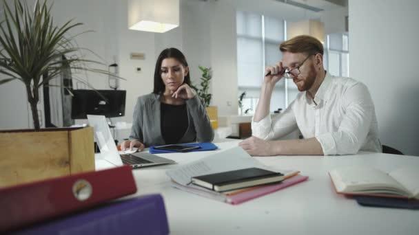 Zaměstnanci, diskutovat o práci v kanceláři. Při pohledu na notebook dohromady