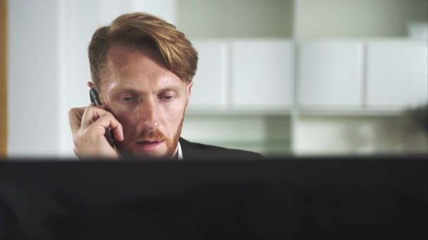 Red-haired man sitting at a computer and calling on the phone