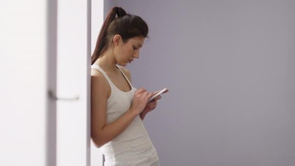 Dívka v tělocvičně vypadá bílý telefon
