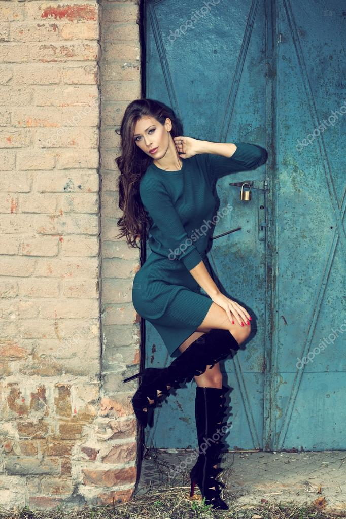 995cf820a6794c Mooie jonge vrouw in korte jurk en hoge hakken laarzen tegen de muur en de  oude metalen deur