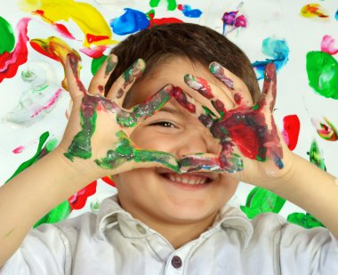 Little boy painting with hands with different color paint on his palms stock vector