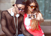 Young fashion couple taking selfie in the city