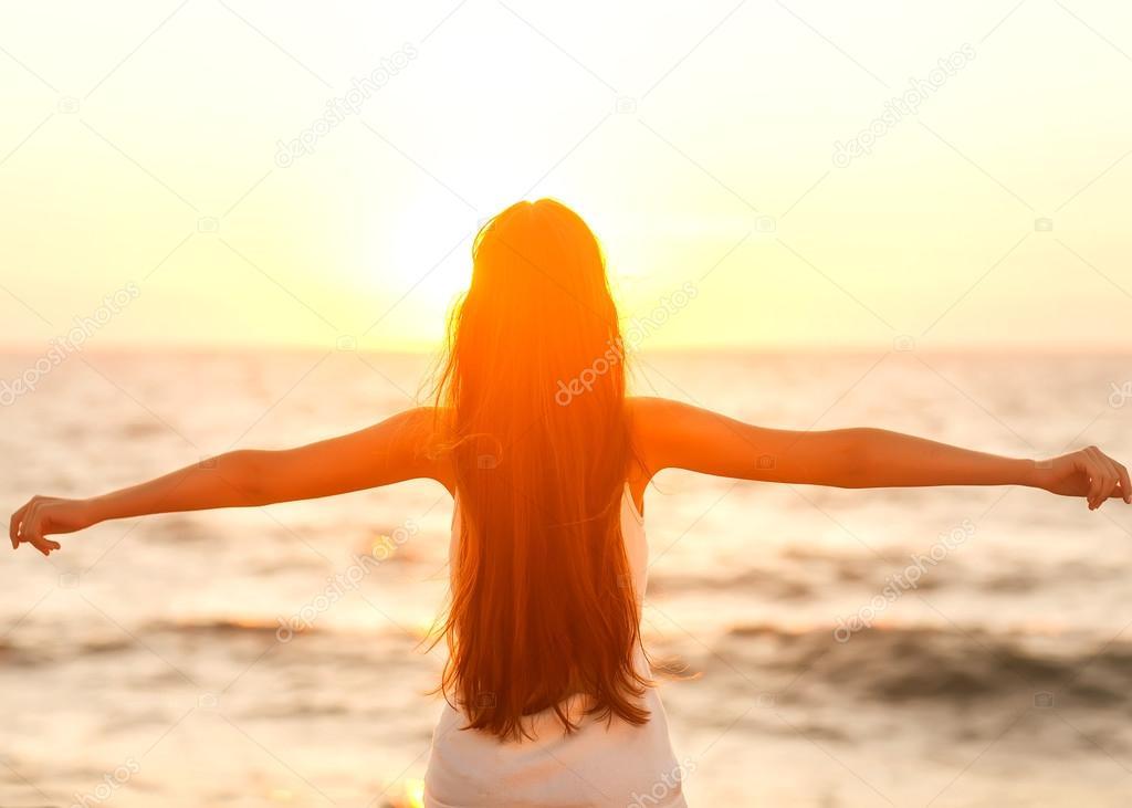 Free woman enjoying freedom feeling happy at beach at sunset.