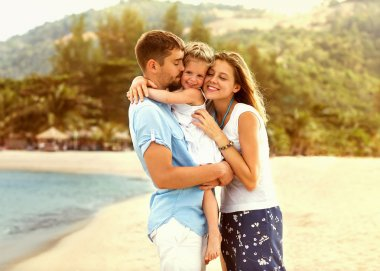 happy family walking on the sea on the beach