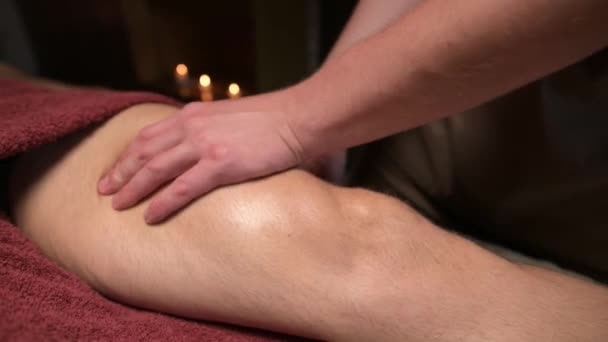 Közelkép Férfi masszőr csinál sport masszázs a combok a lábak, hogy egy izmos sportoló egy irodában egy halvány fény