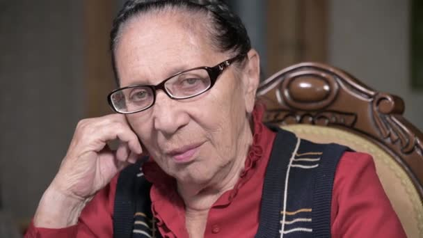 Traurige alte nachdenkliche Frau mit Brille sitzt drinnen auf einem Stuhl und blickt geheimnisvoll in die Kamera. Ältere Probleme
