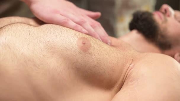 Detailní masáž prsního svalu atletovi, kterého klient masíruje