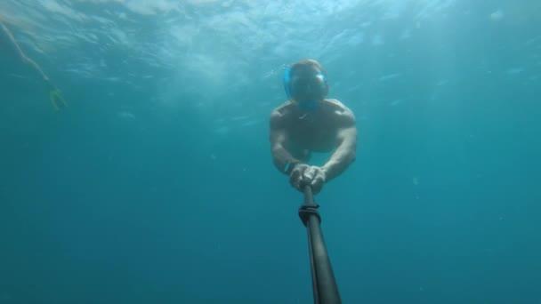 Ein sportlicher junger Mann in Maske und Schnorchel mit Flossen schwimmt unter Wasser.