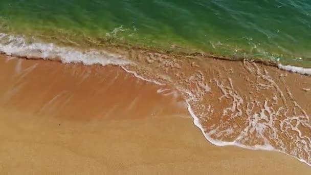Vzdušný pohled shora na mořské modré vlny narážející na pláž. Mořské vlny a krásné písečné pláže letecký pohled záběr z drone.