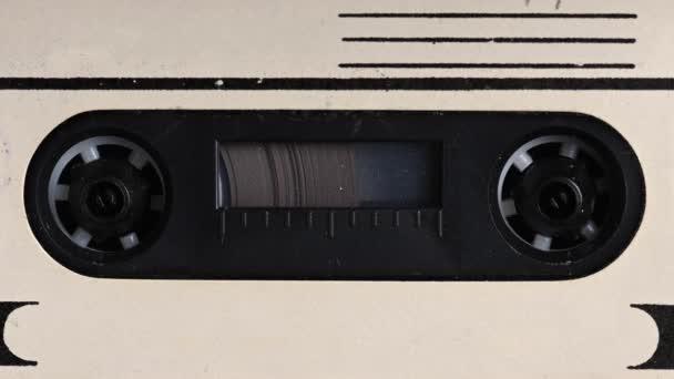 Közelkép Egy magnó lejátszik egy hangkazettát. Közelkép. Egy vintage hangkazetta forog egy üres szalagon, amit arra használnak, hogy hangot rögzítsenek egy retro kazettás lejátszóban. A beszélgetések rögzítése.