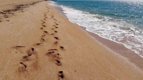 Légi kilátás a forgalomra az arany kagyló strand és az azúrkék tenger felett. Két ember lábnyomai a homokban.