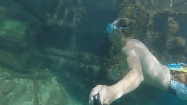 Freitauchender junger Mann in Maske schwimmt unter Wasser neben einem versunkenen Boot. Selfie-Stick-Action-Kamera