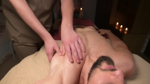 Professional massage of the pectoral muscles for a man to an athlete in a massage parlor
