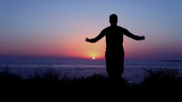 člověk se modlí u moře při západu slunce