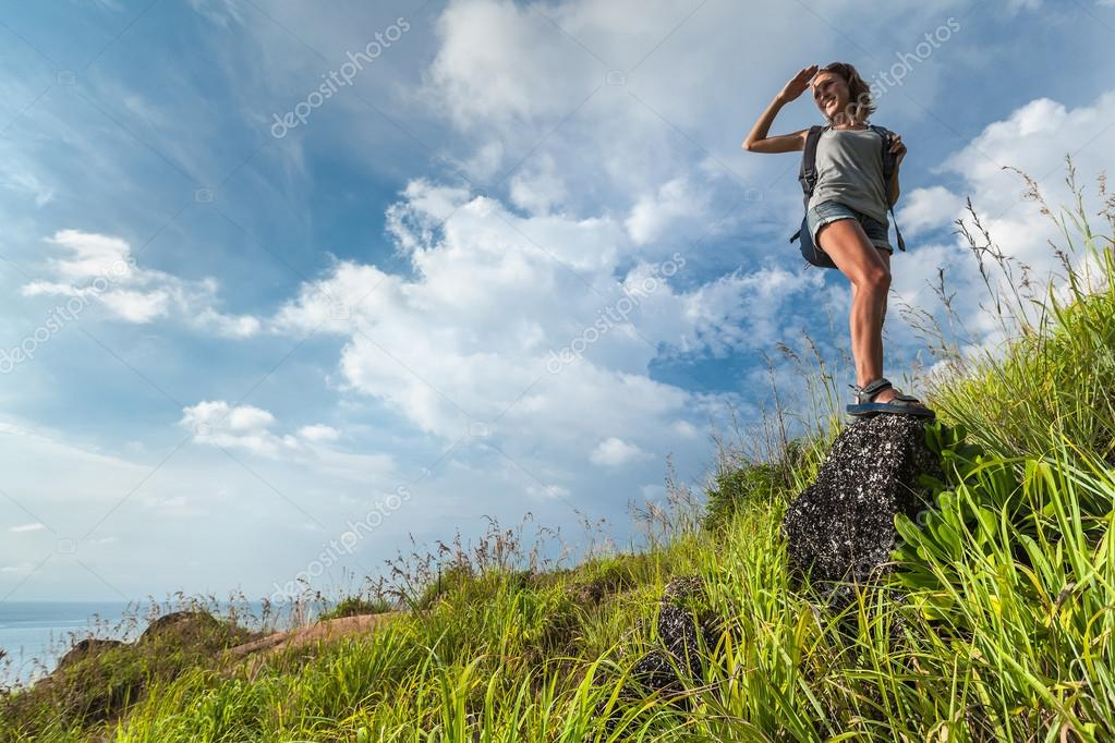 Lady hiker on the green meadow
