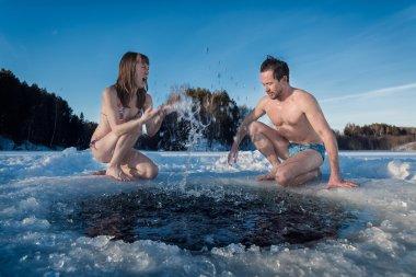 couple splashing the water of a winter lake