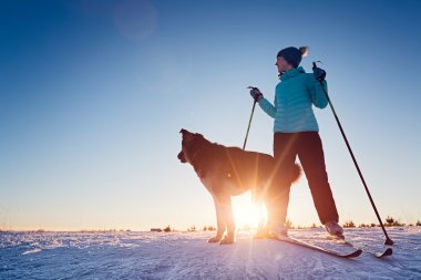 Woman skiing with the dog