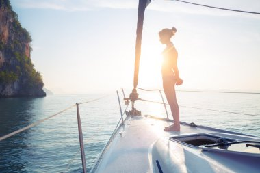 Young lady standing on the bow of yacht