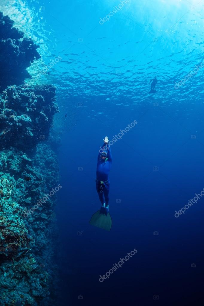 Free diver ascending along the coral reef