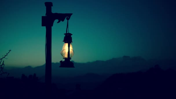 Lantern at twilight with mountains in the background. Cinemagraph seamless loop.