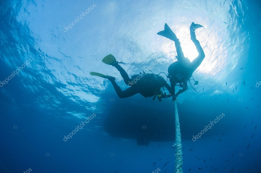 Divers decompressing underwater on a rope