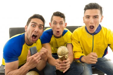 Three friends sitting on sofa wearing yellow sports shirts screaming cheering at camera with enthusiasm, white background, shot from above